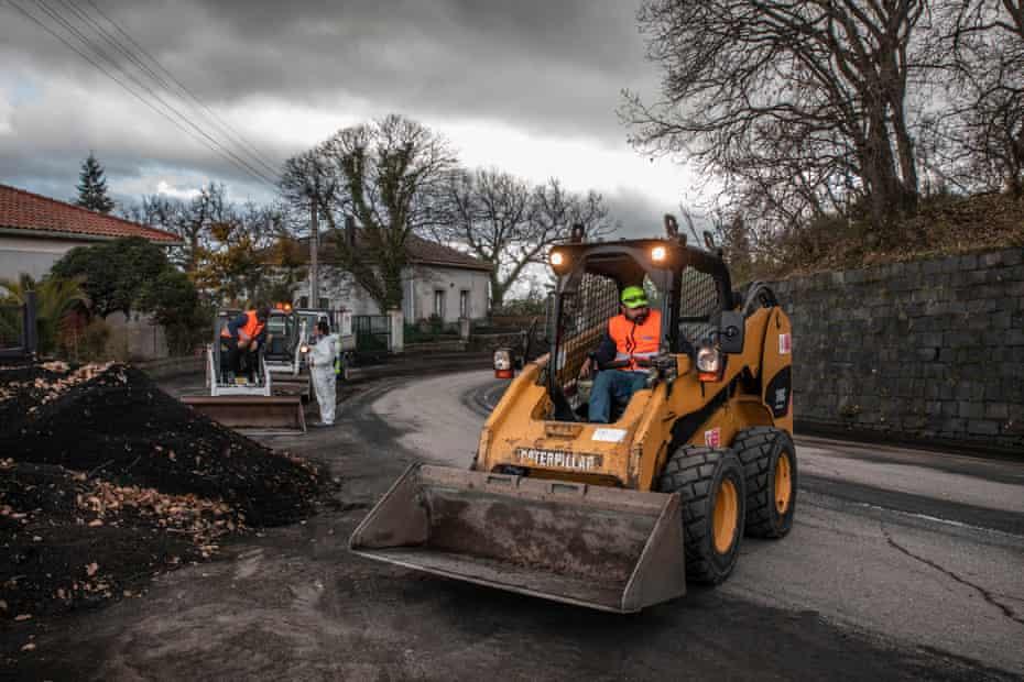 Trabajadores cerca del pueblo de Zafferana Etnea limpian la arena volcánica de las calles principales