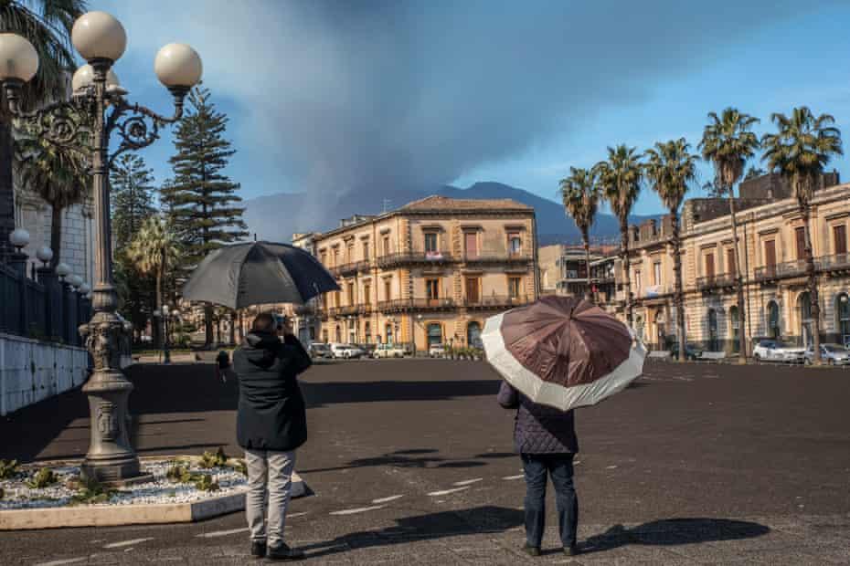 Los habitantes de la localidad de Giarre utilizan paraguas como protección contra las cenizas volcánicas.