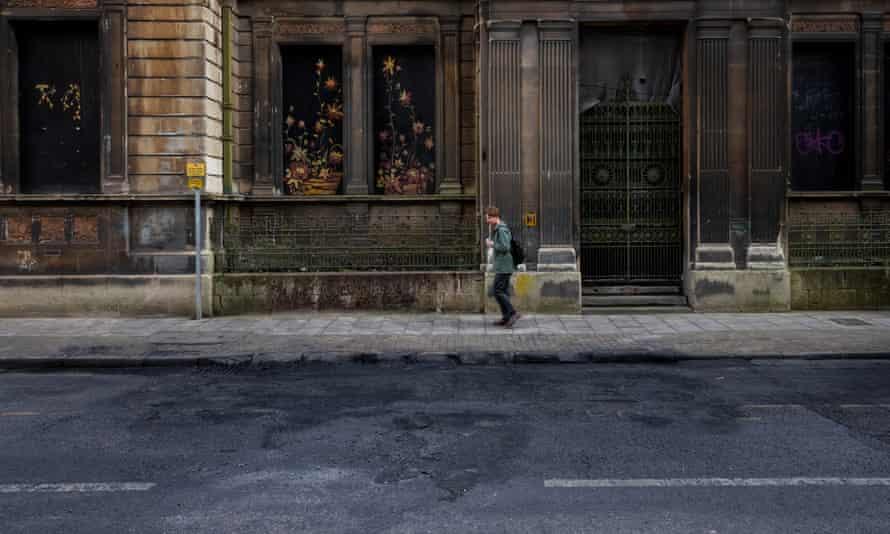 Un hombre pasa junto a los restos de una camioneta de policía derretida en la carretera frente a la estación de policía de Bridewell.