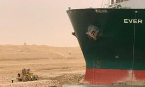 Los trabajadores se ven junto al buque portacontenedores que fue golpeado por un fuerte viento y encalló en el Canal de Suez
