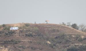 Un partidario de la India ondea su bandera desde una colina que domina el estadio.