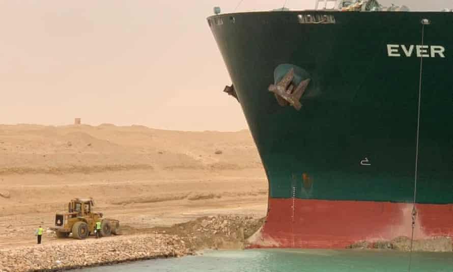 Los trabajadores se ven junto a un buque portacontenedores que fue golpeado por un fuerte viento y encalló en el Canal de Suez