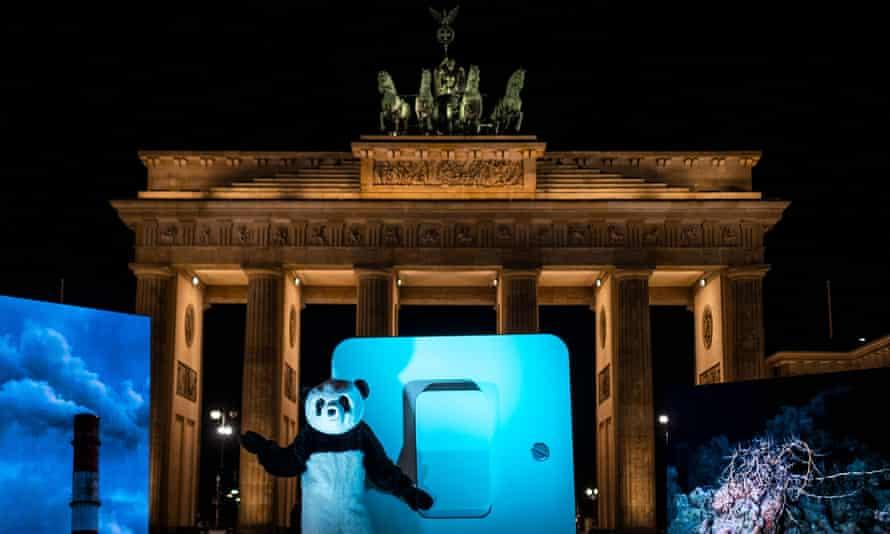 Un activista de WWF vestido con un disfraz de Panda se prepara simbólicamente para encender un interruptor gigante para apagar la iluminación en la Puerta de Brandenburgo en Berlín.