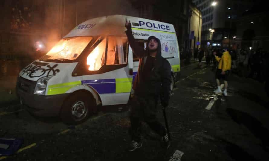 Un manifestante hace un gesto frente a un vehículo policial en llamas durante la protesta.