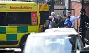 La gente se reúne alrededor de una ambulancia estacionada fuera de la entrada trasera del Hospital King Edward VII