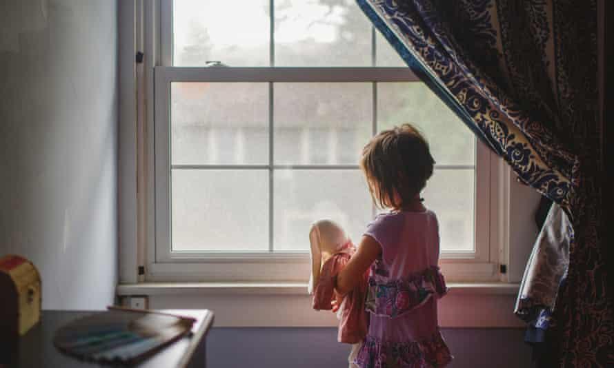 Un niño pequeño se encuentra junto a la ventana del dormitorio sosteniendo tiernamente un conejo de peluche