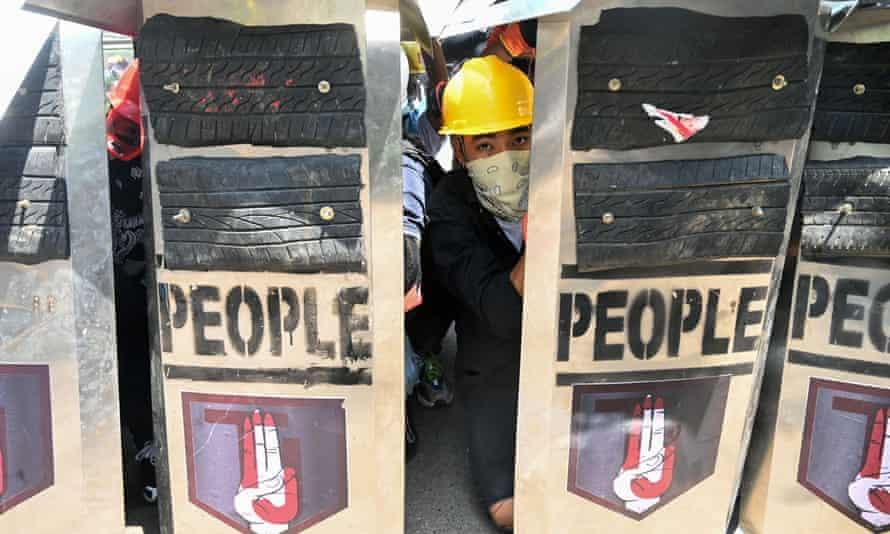 Un manifestante mira detrás de sus escudos durante una manifestación contra el golpe militar en Yangon el domingo.