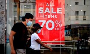 Los compradores que usan mascarillas o mantas debido a la pandemia de COVID-19 pasan junto a los carteles de ventas en el escaparate de una tienda en Londres en agosto pasado