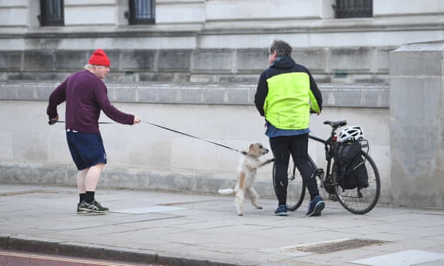 Boris Johnson con su perro y un transeúnte