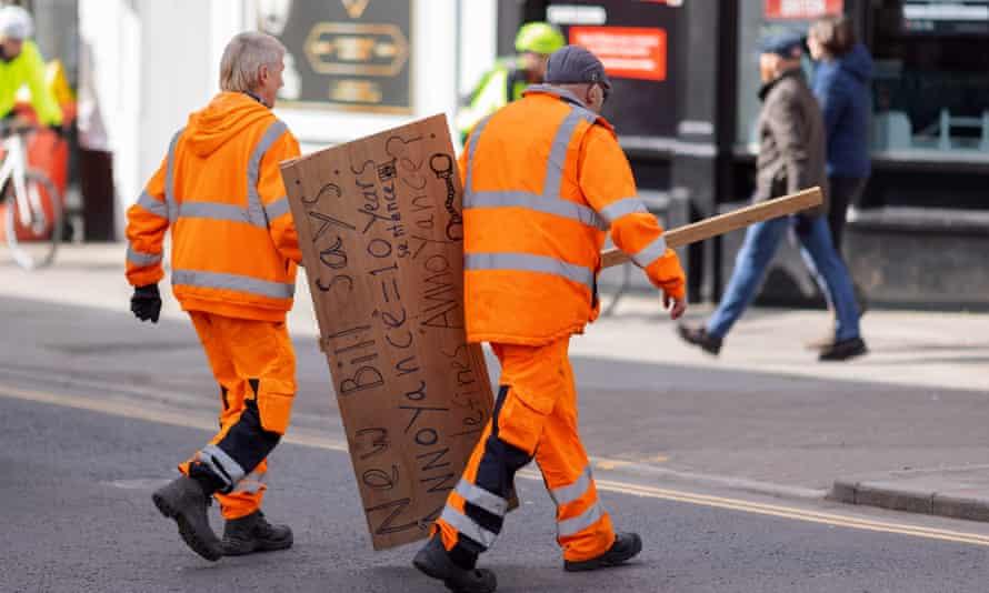 Los trabajadores retiran un cartel dejado por los manifestantes