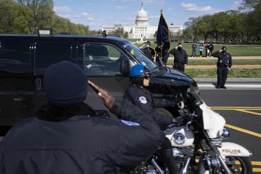 Los oficiales de la Policía del Capitolio saludan mientras una procesión lleva los restos del oficial asesinado.