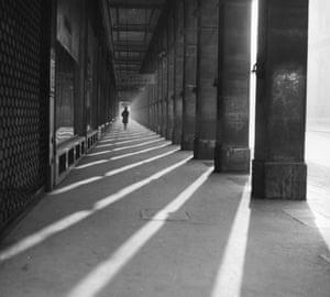Arcada parisina, alrededor de 1950: una mujer camina junto a los grandes pilares de la arcada en el extremo oeste de la rue Rivoli, París.