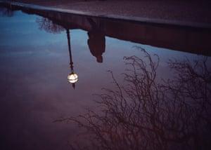 La foto muestra el reflejo de una figura en un charco mientras camina por una calle de la ciudad a altas horas de la noche.