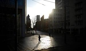 Un peatón camina por una plaza de San Pedro vacía en Manchester, noroeste de Inglaterra, el 5 de enero de 2021.