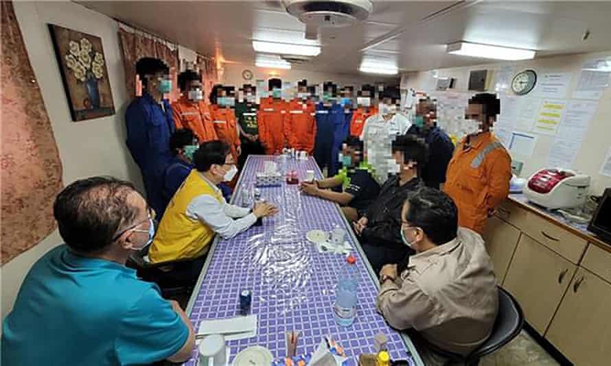 Un funcionario surcoreano (vestido con un chaleco amarillo) se reúne con la tripulación del Hankuk Chemi.