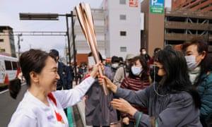 Los espectadores tocan la antorcha llevada por el portador de la antorcha Junko Ito en el segundo día del Relevo de la Antorcha Olímpica en Fukushima, Japón, el 26 de marzo de 2021.