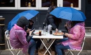 Personas en el centro de la ciudad de Cardiff en el día festivo del lunes cuando la lluvia caía y las temperaturas caían en picado.
