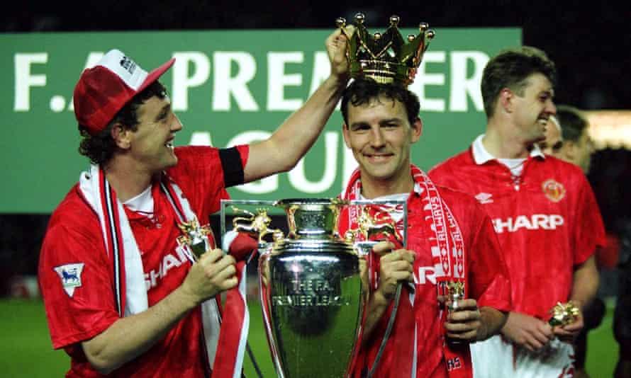 Steve Bruce corona a Bryan Robson después de la victoria del Manchester United en la Premier League en mayo de 1993.