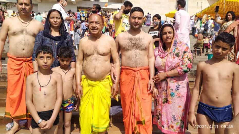 Thakur Puran Singh, de amarillo, de pie en la orilla del Ganges con su familia durante el Kumbh.