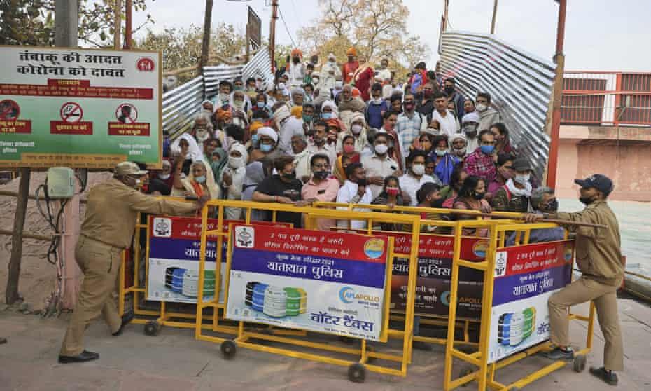 Los adoradores se paran detrás de las barricadas mientras esperan que Naga Sadhu o santos hindúes desnudos lleguen para Shahi snan o un baño real durante Kumbh mela, en Haridwar, el 12 de abril.