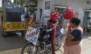 Un trabajador de un hospital privado que lleva un casco con el tema del coronavirus Covid-19 conduce su motocicleta para asesorar a las personas en los mercados y barrios marginales sobre las medidas de precaución que deben tomar contra la propagación del coronavirus en Hyderabad el 31 de mayo de 2021 (Foto de Noah SEELAM / AFP) ( Foto de NOAH SEELAM / AFP a través de Getty Images)