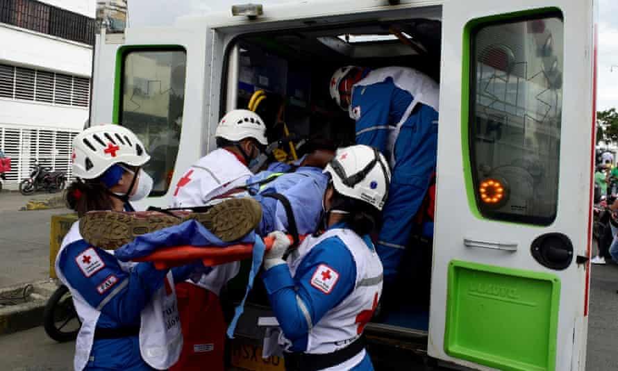 Paramédicos de la Cruz Roja llevan el cuerpo de un agente de la Unidad de Investigaciones de la Fiscalía General, que abrió fuego contra civiles antes de ser asesinado.