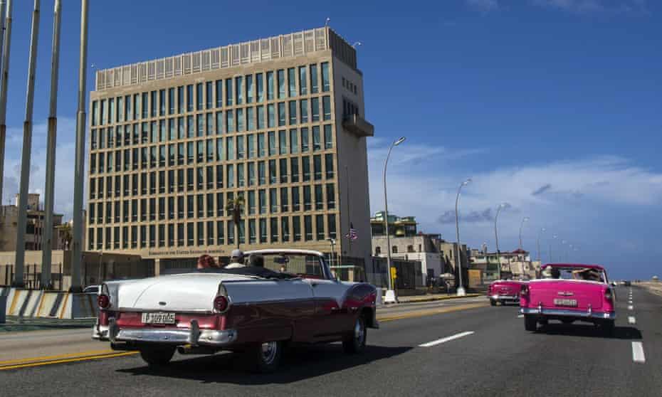 Los turistas conducen autos convertibles clásicos en el Malecón junto a la Embajada de los Estados Unidos en La Habana, Cuba.