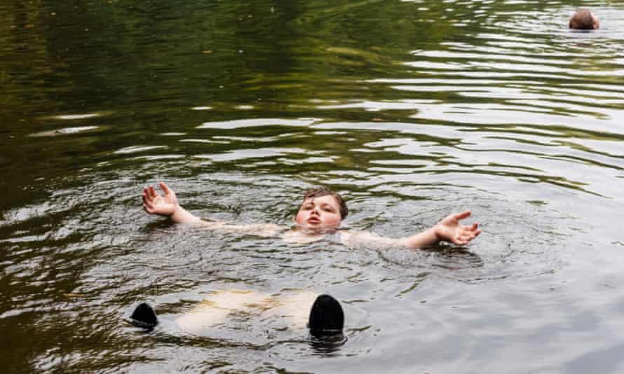 Niño llamado Dominic flotando de espaldas en un lago mientras nada en la naturaleza