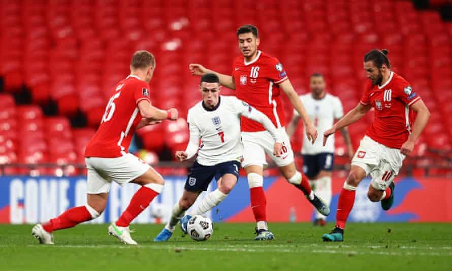 Phil Foden de Inglaterra corre con el balón bajo la presión de Jakub Moder y Grzegorz Krychowiak de Polonia