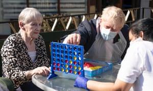 Boris Johnson juega un juego de mesa con los residentes de los hogares de ancianos del este de Londres. Fotografía: Paul Edwards / WPA / Getty