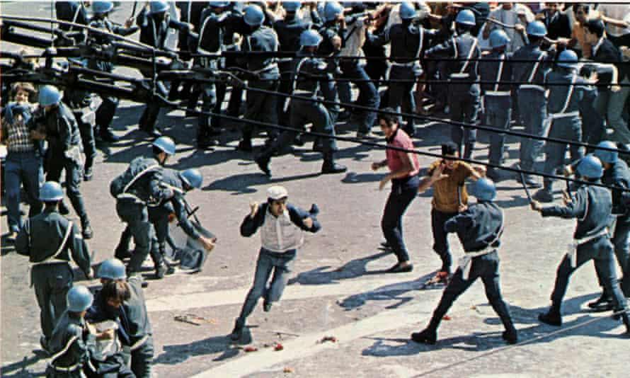 Hombre agitando ambos puños cruza la falange de la policía antidisturbios, visto desde arriba