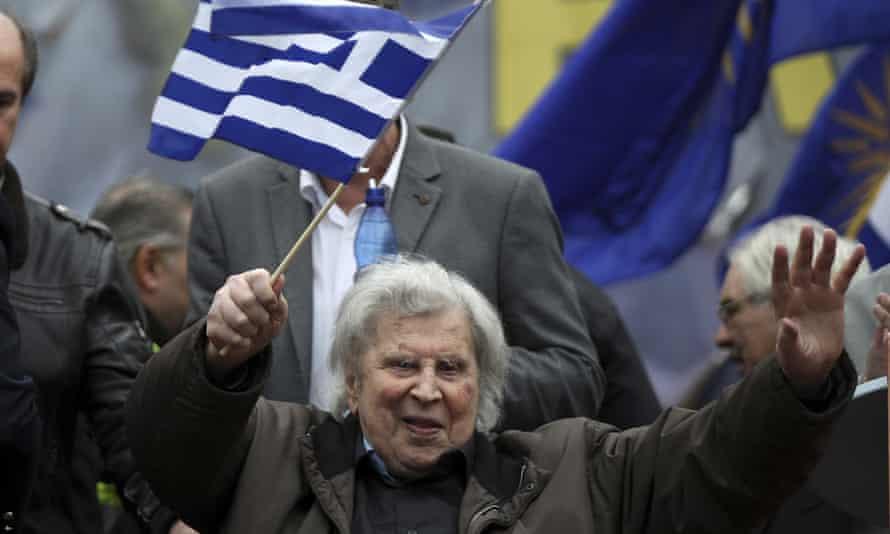 Theodorakis en la vejez, sosteniendo ambas manos para saludar a la multitud, con una bandera griega azul y blanca en un palo en una mano