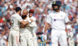 Moeen Ali celebra con James Anderson después de tomar el wicket de Indian Virat Kohli