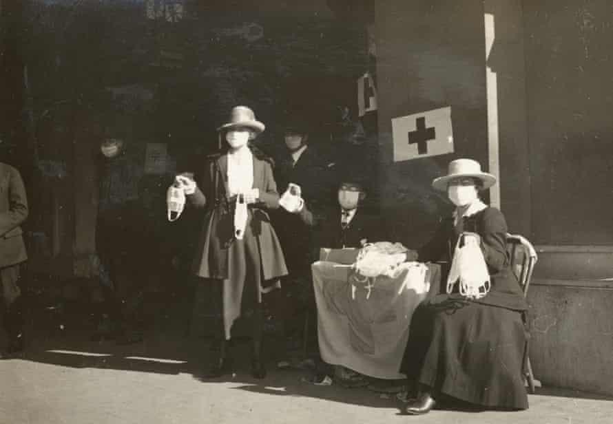 Los voluntarios de la Cruz Roja distribuyen máscaras contra la gripe en una mesa en San Francisco en 1918.