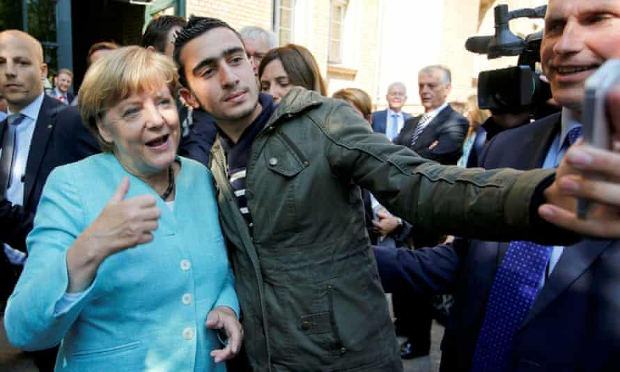 Un refugiado sirio se toma una selfie con Angela Merkel en Berlín en 2015.