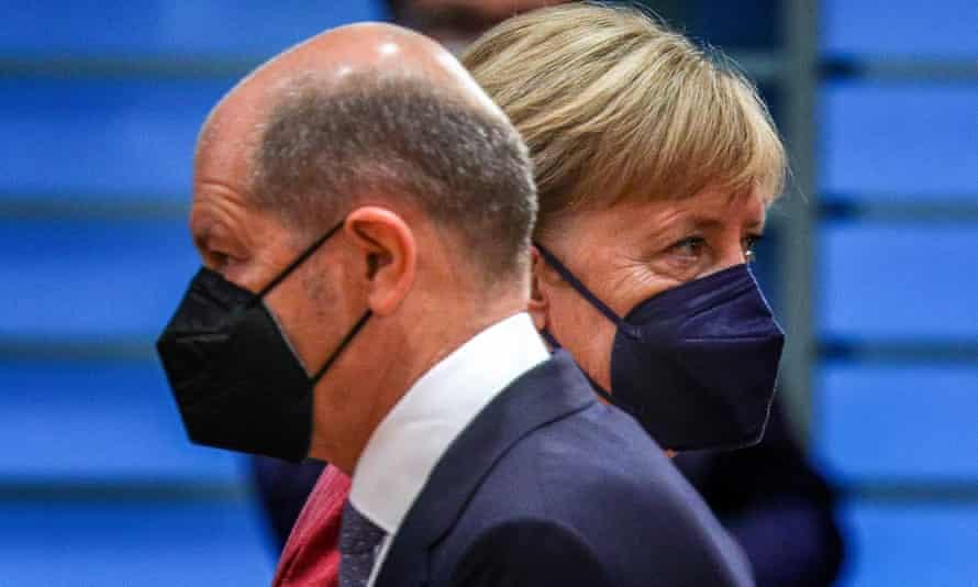 El ministro de Finanzas alemán, Olaf Scholz, se cruza con Merkel.
