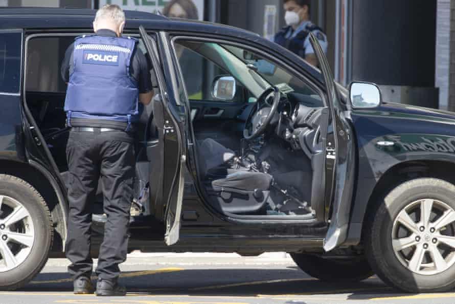 La policía inspecciona un vehículo fuera del supermercado donde un hombre fue asesinado a tiros después de apuñalar a varios compradores.