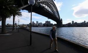 Se ve a una persona haciendo ejercicio temprano en la mañana bajo el Puente del Puerto de Sydney en Sydney, Australia.