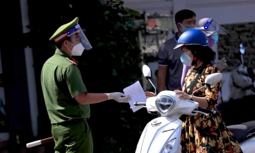 Oficial de policía entrega el permiso de viaje a un pasajero en el puesto de control de Vung Tau