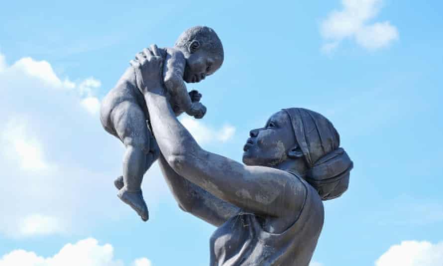 Cerca de una estatua de bronce naturalista de una mujer negra con un pañuelo sosteniendo a un bebé en alto y mirándola a los ojos