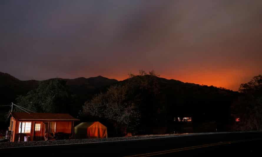 El resplandor del incendio del complejo KNP que arde en el Parque Nacional Sequoia se puede ver en las colinas detrás de las casas en Three Rivers, California.