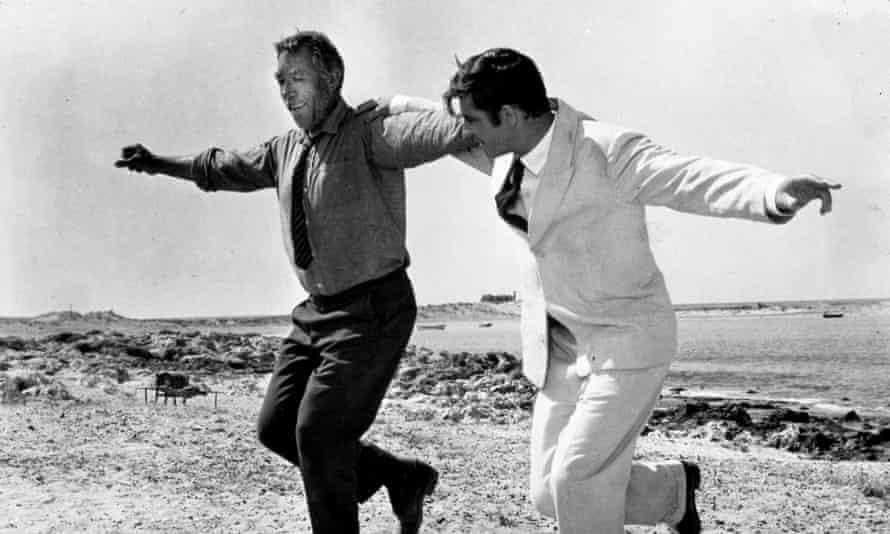 Foto fija de dos hombres en traje con sus brazos alrededor de sus hombros bailando