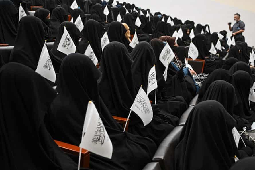 Estudiantes con velo ondean banderas talibanes mientras escuchan a un orador antes de una manifestación a favor de los talibanes en la Universidad de Educación Shaheed Rabbani en Kabul el 11 de septiembre.